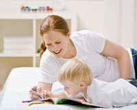 Devoted mother coloring in coloring book with son. On bed in bedroom Stock Image