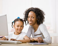 Devoted mother helping daughter do homework. On computer Royalty Free Stock Photos