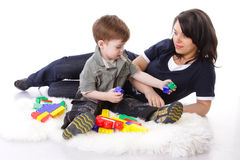 Devoted mother playing with colored blocks. With her curious son Stock Photos