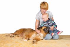 Devoted Mum, baby and family dog. Devoted Mum, small baby and family dog sitting on the floor close together sharing a moment of love and tenderness with Royalty Free Stock Image