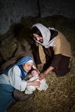 Devoted parents in Christmas nativity scene. Live Christmas nativity scene in an old barn - Reenactment play with authentic costumes.  The baby is a property Stock Images