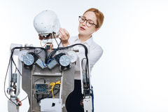 Devoted precise woman making sure the robot working right Royalty Free Stock Photography