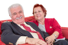 Devoted senior couple seated on a red sofa Royalty Free Stock Image