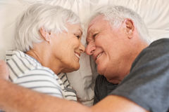 Devoted senior couple smiling warmly at each other in bed. Content senior couple smiling happily at each other while lying face to face in their bed together in Royalty Free Stock Images