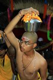 A devotee in the Hindu festival of Thaipusam. A devotee with bells pierced into his skin in the Hindu festival of Thaipusam Stock Photos