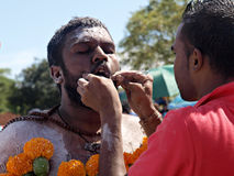 A devotee at a Kavady festival has his mouth pierced Royalty Free Stock Photo
