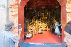 Devotee kneels at feet of monk inside temple. CHIANG MAI, THAILAND - JANUARY 26, 2017; Devotee kneels at feet of monk inside temple where money tree can be seen Royalty Free Stock Photo