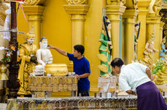 Devotee pours water over the Buddha statue and offer incense at Shwedagon Pagoda Royalty Free Stock Photo