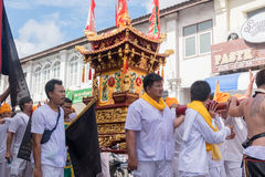 Devotees of a Chinese Taoist shrine carry a palanquin housing a Royalty Free Stock Photos