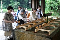 Devotees performing harai before worship at Meiji Shrine, Tokyo, Japan. The devotees performing harae or harai before worship on the water reservoir at Meiji stock photography