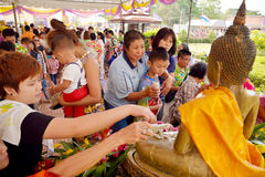 Devotees at Songkran Festival. Thai people pouring water to gold Buddha statue during Songkran Festival  - water festival - 2015 at temple in Ayutthaya, Thailand Stock Photos