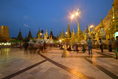 Devotees standing & sitting at Crowded Shwedagon Pagoda in the evening during sunset royalty free stock image