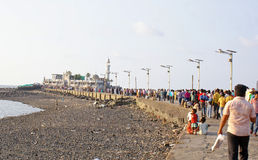 Devotees and tourists on way to Haji Ali Mosque. Located off the coast from Arabian Sea,in Mumbai,India Stock Photo