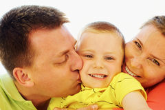 Devotion. Portrait of happy kid being kissed by his parents royalty free stock image