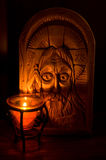 Devotion. The small candle faces to a wooden icon Royalty Free Stock Image