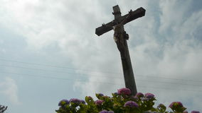 Devotion cross along the way. A devotion cross with christ along the way in a little village at the countryside in Normandy, France. A low shot. Some pink stock video footage