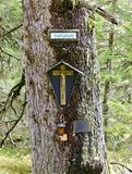 Devotion place with crucifix. On the trunk of a tree in a forest at Tirol, Austria stock photos