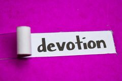 Devotion text, Inspiration, Motivation and business concept on purple torn paper royalty free stock photos