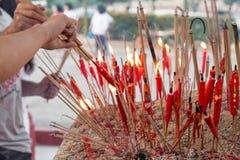 Devoto chino del taoist que se enciende encima de velas en el templo Imagenes de archivo
