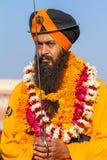Devoto sikh con el turbante y las flores anaranjados Imagen de archivo libre de regalías