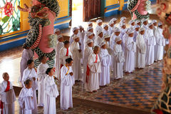 Devotos de las mujeres que ruegan en el templo de Cao Dai Imagenes de archivo