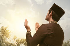 Devout asian muslim man praying with his both hands. With sunset background stock photography