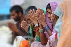Devout Hindu pilgrims in Maheshwar, India. Devout Hindu pilgrims pray on the ghats of the sacred river Narmada in Maheshwar, India royalty free stock image