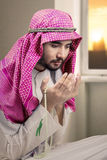 Devout male praying at home. Portrait of devout man is wearing Islamic clothes while praying to the Allah at home stock images