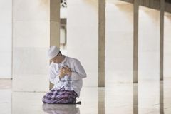 Devout Muslim man looks sad in the mosque. Portrait of a devout Muslim man looks sad while praying in the mosque stock photos