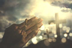 Devout person praying with rosary. Image of hands of devout person praying to the GOD while holding a rosary with crucifix symbol royalty free stock images