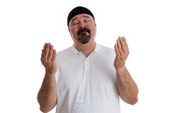 Devout religious man deep in prayer. Devout religious middle-aged man deep in prayer standing with is eyes closed and hands raised in supplication, isolated on royalty free stock photo