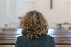 Devout religious woman praying in a church. Back view of a Devout religious middle-aged woman praying in a church kneeling alone in a pew royalty free stock image