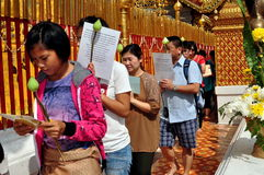 Chiang Mai,TH: Devout Worshippers at Thai Temple. Devout Thais carrying prayer cards and Lotus flower buds in procession around the sacred golden Chedi at Wat stock photos