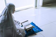 Devout woman reading Quran after doing Salat. Close up of a devout woman reading Quran after doing Salat near the window at home stock photos