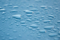 Dew drops on blue metallic surface Stock Photos