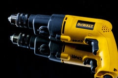 DeWalt drill on a black background. Heave duty hammer drill by DeWalt lying on a mirror with a reflection Stock Images