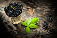 Dewberries i metall bowlar på tappningträbräde royaltyfria bilder
