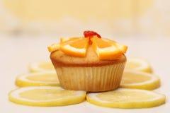 Dewlicious-Muffin mit einem Stück der Erdbeere auf die Oberseite umgeben durch geschnittene gelbe Zitronen lizenzfreies stockbild