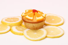 Dewlicious muffin with a piece of strawberry on top surrounded by sliced yellow lemons Stock Photo