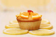Dewlicious muffin with a piece of strawberry on top surrounded by sliced yellow lemons Royalty Free Stock Image
