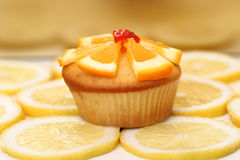 Dewlicious muffin with a piece of strawberry on top surrounded by sliced yellow lemons Royalty Free Stock Images