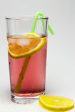 Dewy glass of juice with ice, and lemon. Stock Photo