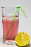 Dewy glass of juice with ice, and lemon. Royalty Free Stock Image