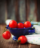 Dewy red tomatoes in blue bowl Stock Photos