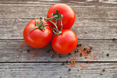 Dewy red tomatoes with pepper on old wooden table Stock Images