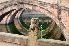 Deyang, China: Pan Bridge at Confucian Temple. A carved lion sits atop a balustrade and the reflected arches of the three Pan Bridges over the Pan Pond at the Royalty Free Stock Images