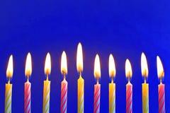 Dez amarelos e velas ardentes cor-de-rosa do aniversário no azul imagem de stock