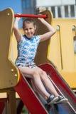 Dez anos de menina idosa têm o divertimento no campo de jogos das crianças ao sentar-se em deslizar a placa Fotografia de Stock