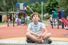 Dez anos de menino estão sentando-se no campo de jogos dos cheldren Fotos de Stock Royalty Free