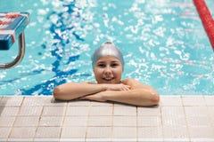 Dez da menina anos de posição do nadador na piscina, olhando a câmera e o sorriso foto de stock